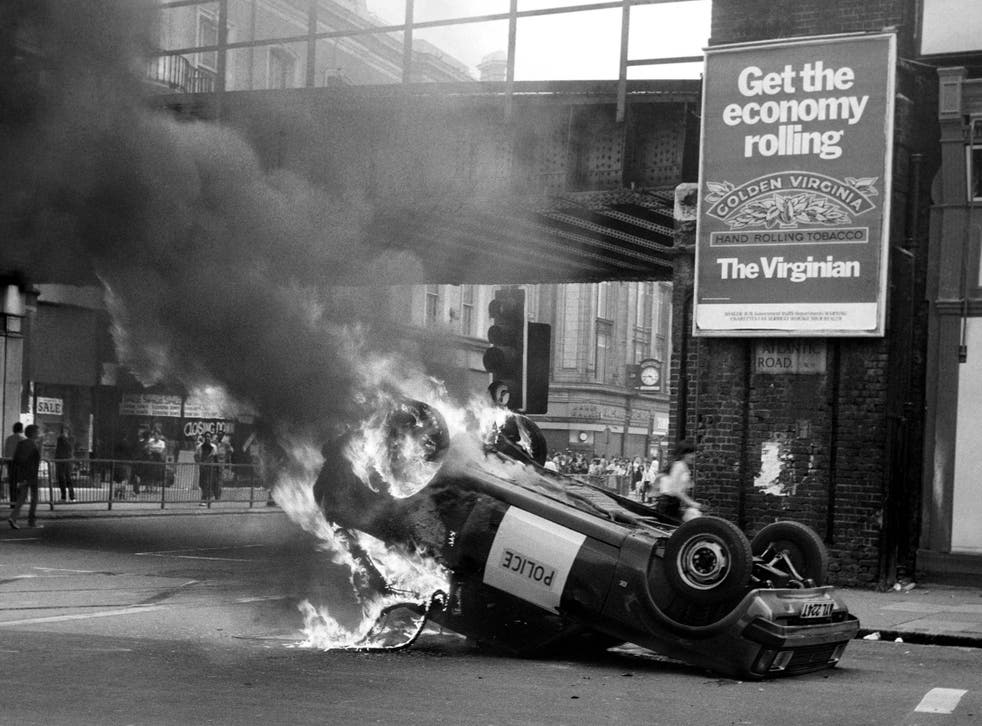 A police car blazes at the corner of Atlantic and Brixton Road during the 1981 riots