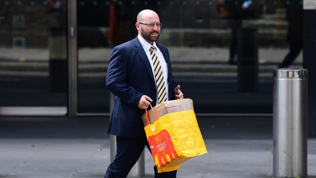 A man leaves the Deutsche Bank offices in London with his belongings in a Sainsbury's bag