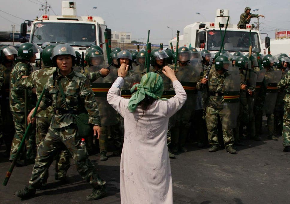 An Uighur woman protests before a group of paramilitary police when journalists visited Xinjiang in July, 2009