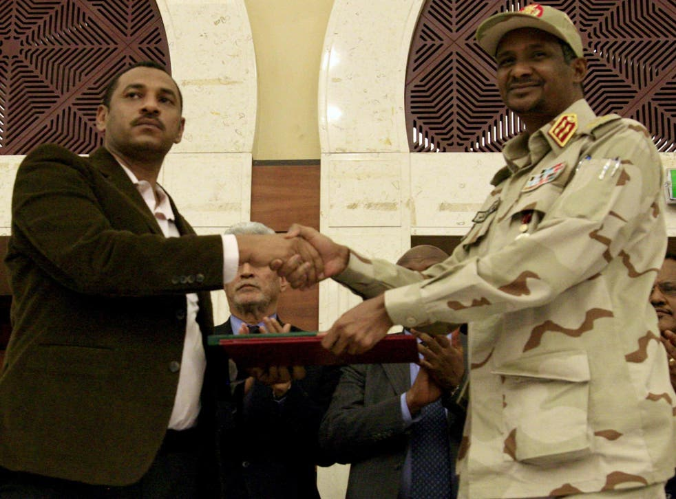 Sudanese deputy chief of the ruling military council and protest movement leader shake hands after inking an agreement