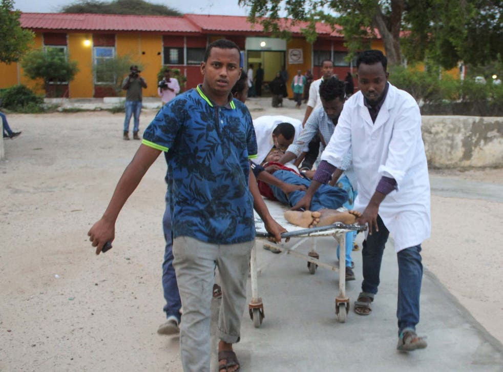 Medics carry a man who was injured in a blast after a suicide bomber walked into the office of Mogadishu's mayor before blowing himself up