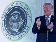 Trump speaks in front of fake seal with Russian eagles and golf clubs