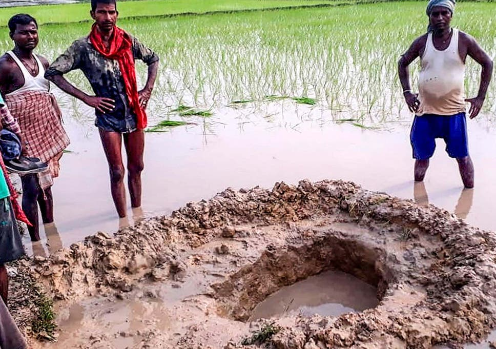 Villagers and farmers pose around the meteorite's crater