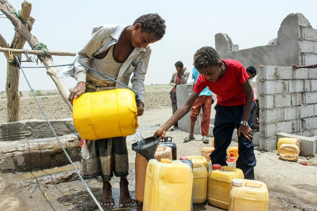 A displaced Yemeni boy collects water from the Red Sea port city of Hodeida