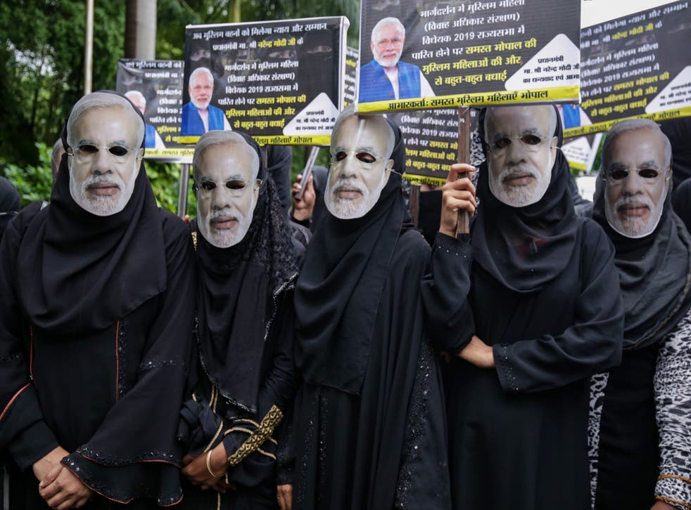 Muslim women wearing face masks of Indian Prime Minister Narendra Modi take part in an event organised by the BJP to celebrate the passage of a law to outlaw triple talaq