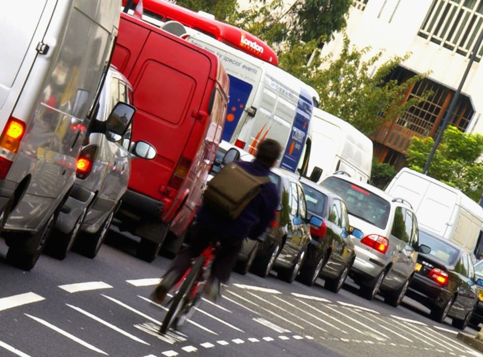 A cyclist make his way through solid traffic in London