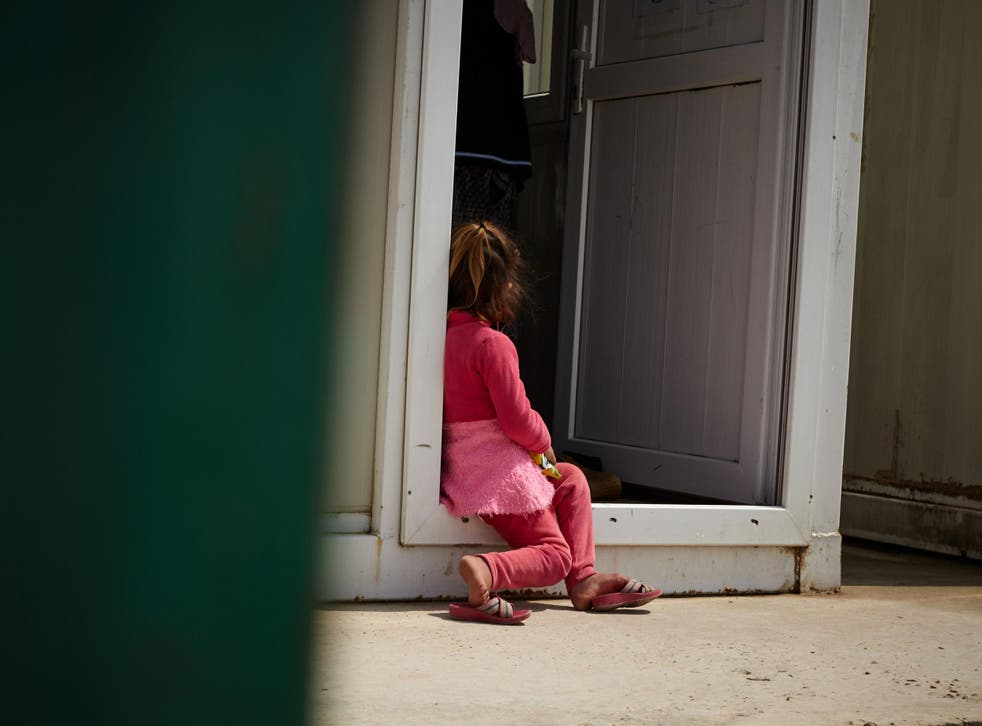 A young girl sits outside the women's centre at a camp in Dohuk in the Kurdish region of Iraq