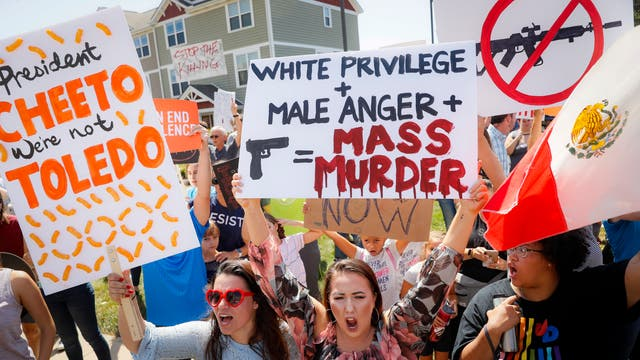 Demonstrators chant as they protest the arrival of President Donald Trump outside Miami Valley Hospital after a mass shooting that occurred in the Oregon District