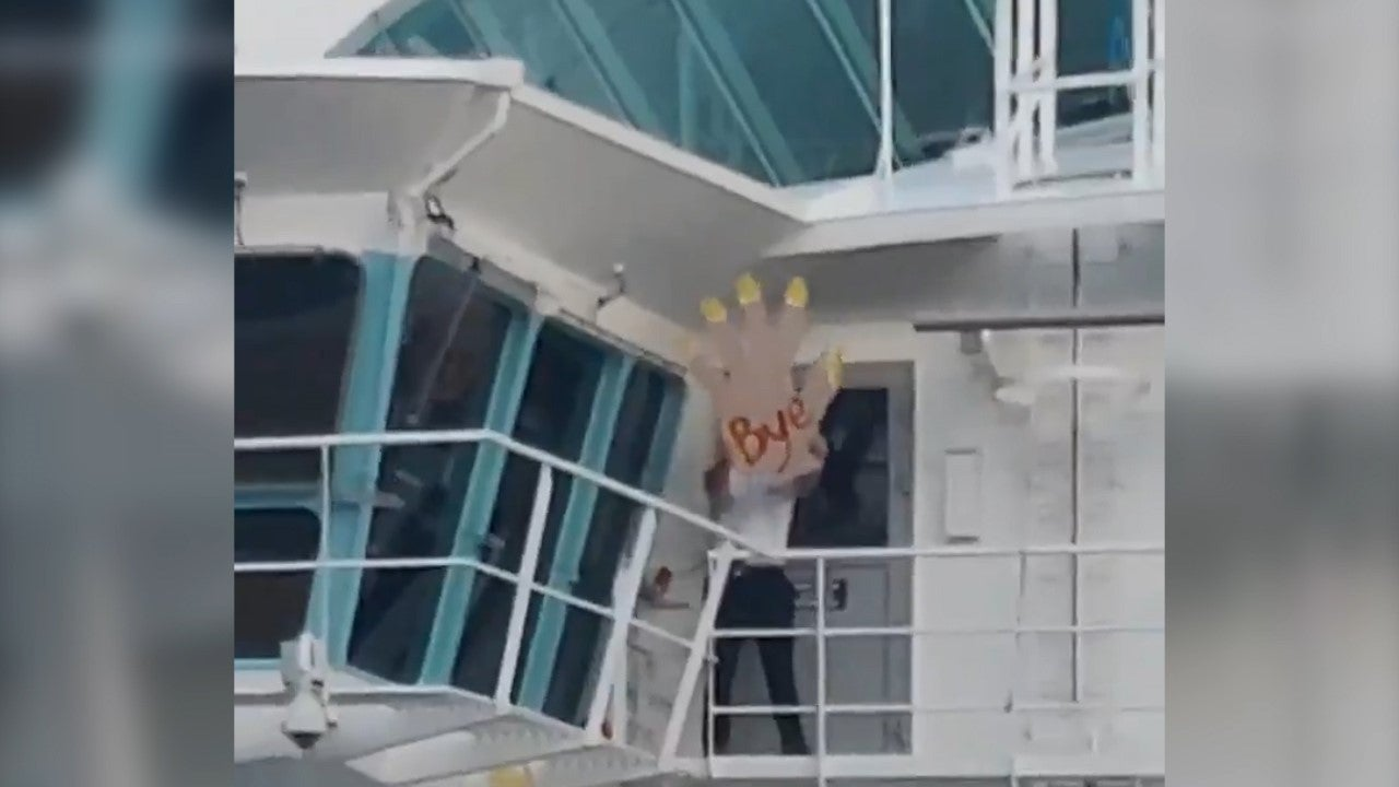 'Absolutely savage' crewman waves with giant foam hand as cruise ship leaves stranded passengers behind