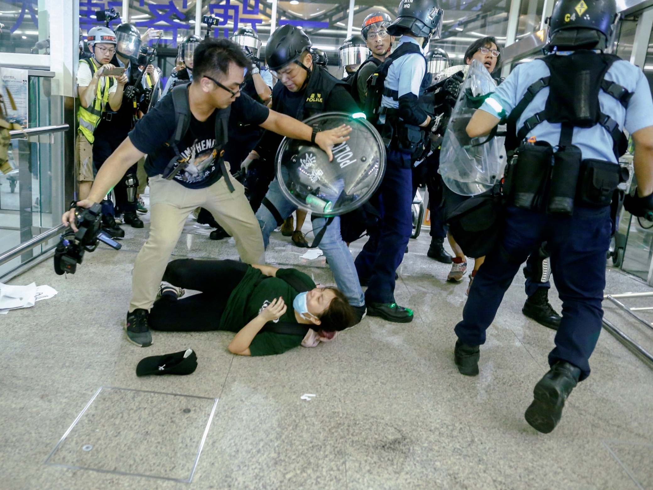 Hong Kong protests - live: Police officer mobbed by crowd pulls gun on protesters amid violent clashes at airport