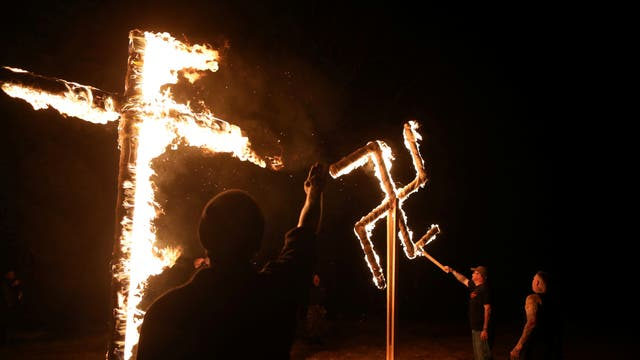 Members of the ShieldWall Network, a white nationalist group, burn a swastika and cross during a party outside Atkins, Arkansas, U.S on March 9, 2019