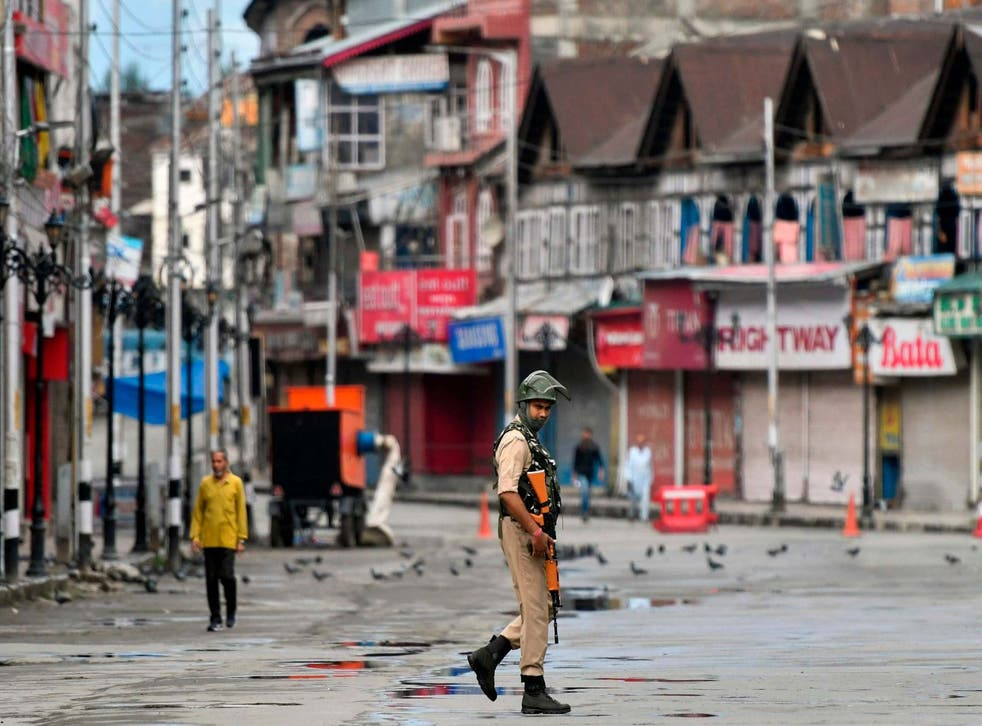 A security forces member patrols a deserted road in Srinagar