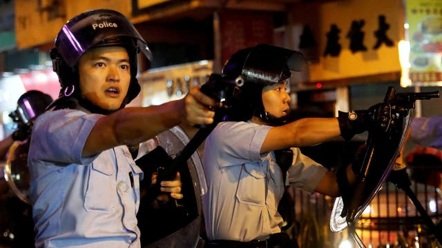 Police officers point their guns towards pro-democracy protesters after a clash at a march in Hong Kong on August 25