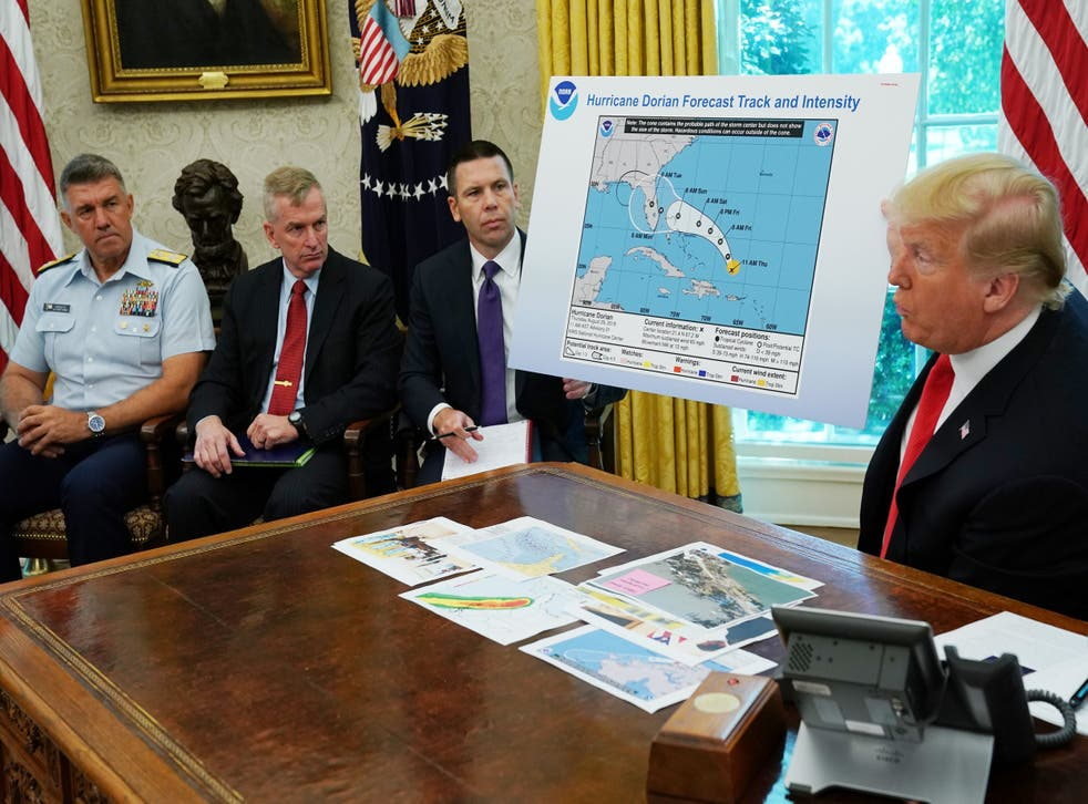 Donald Trump addresses reporters while holding doctored map