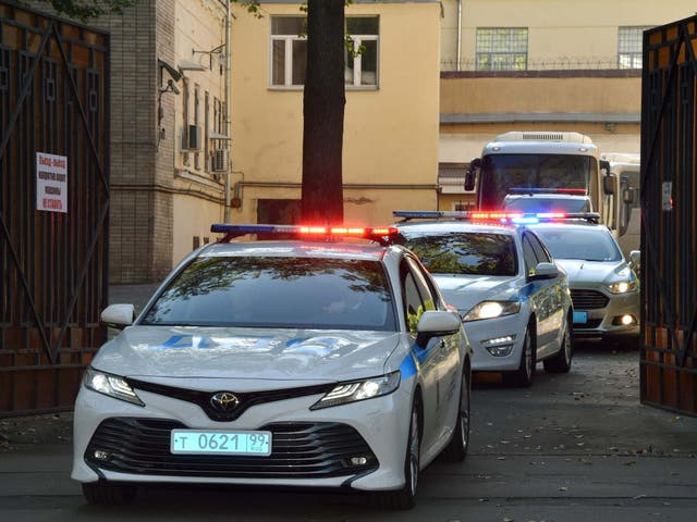 A police convoy escorts two buses with tinted windows leaving the high-security prison of Lefortovo