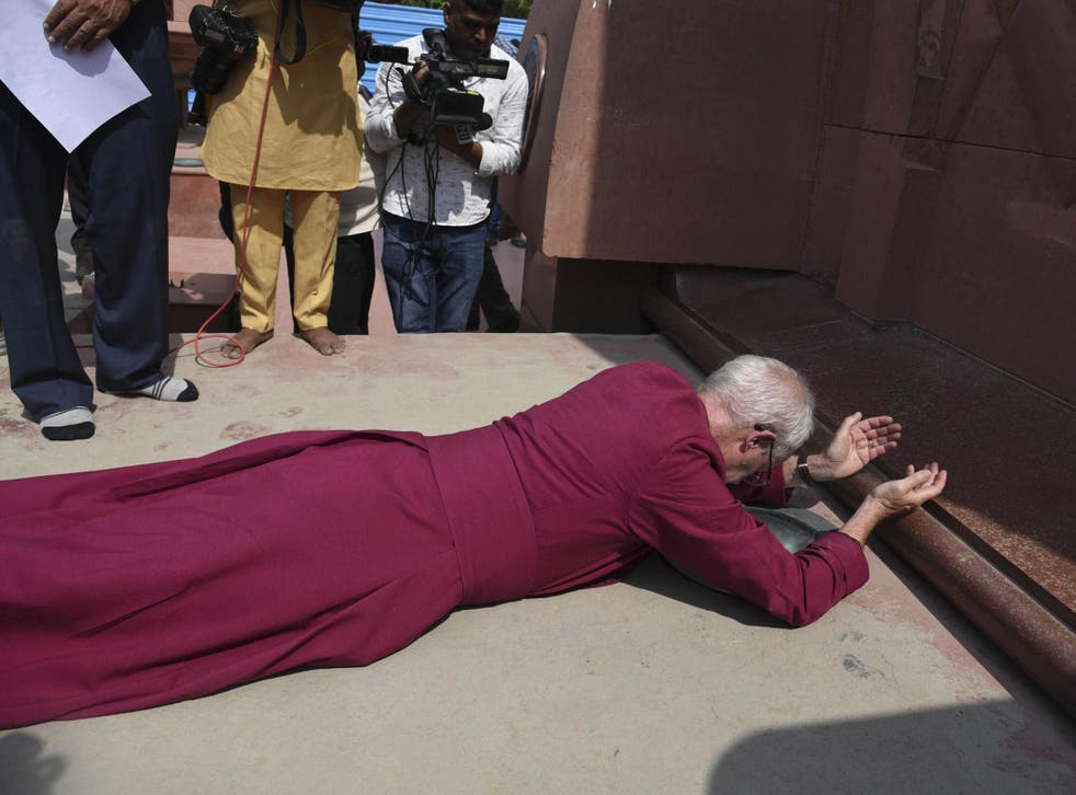 The Archbishop of Canterbury Justin Welby, prostrates as he pays respect at the Jallianwala Bagh memorial