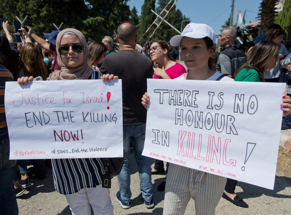 Two Palestinian women hold placards during a rally over the death of Israa Ghrayeb, suspected to have died by honour killing