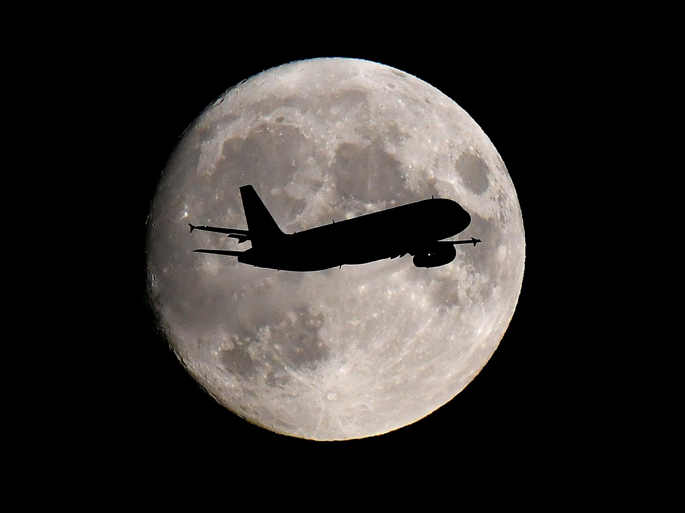 Photographers capture planes flying in front of full moon