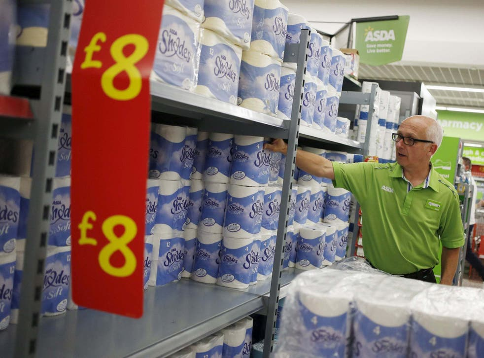 An employee stocks toilet paper along an aisle of an Asda store in Kendal, northwest England.