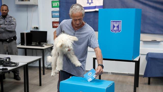 An Israeli man holding his dog casts his ballot