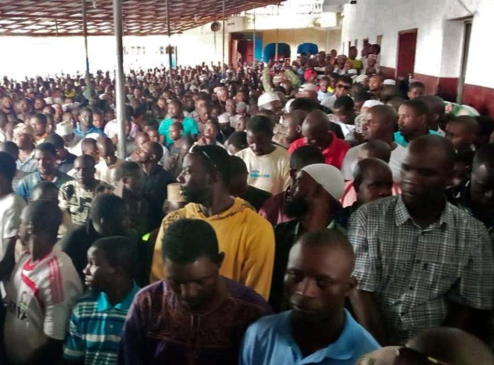 People wait for prayers to begin at a Liberian mosque after a fire swept through a school, reportedly killing dozens of children
