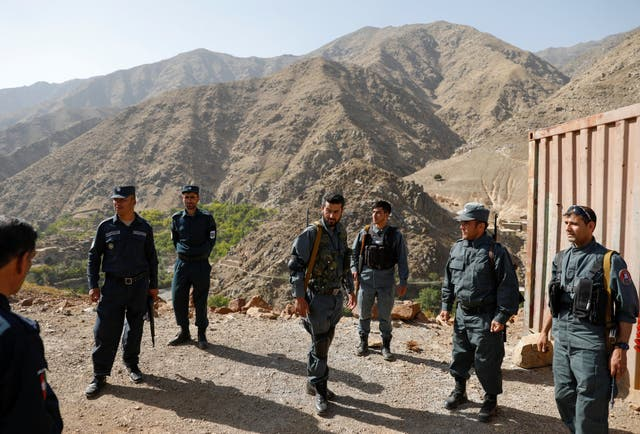 Afghan policemen keep watch as others carry election material to polling stations inaccessible by road, in Shutul, Panjshir province, on Friday
