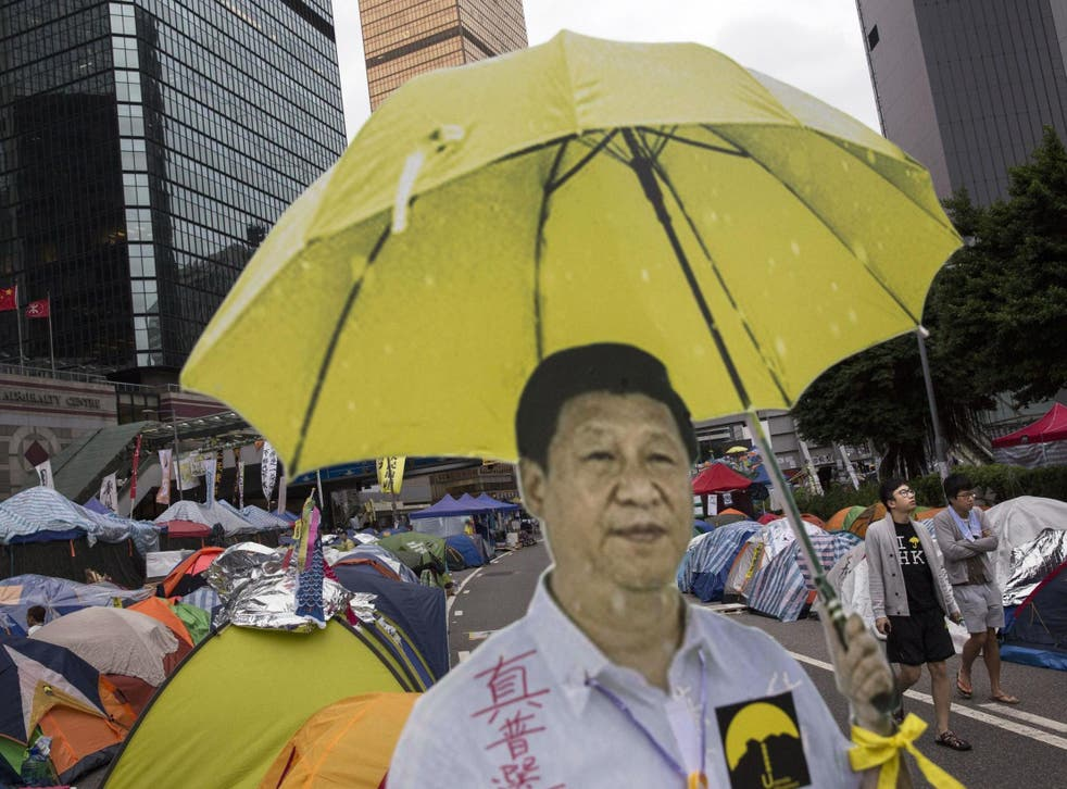 Hong Kong protesters used a cardboard cut-out of Chinese president Xi Jinping holding a yellow umbrella, the symbol of their movement – the real Xi is hoping for blue skies on Tuesday