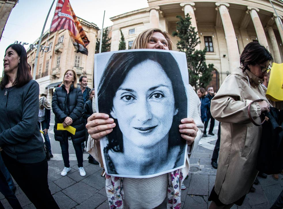 A protester holds a poster of Daphne Caruana Galizia, assassinated in a car bomb attack in 2017, during a vigil demanding justice