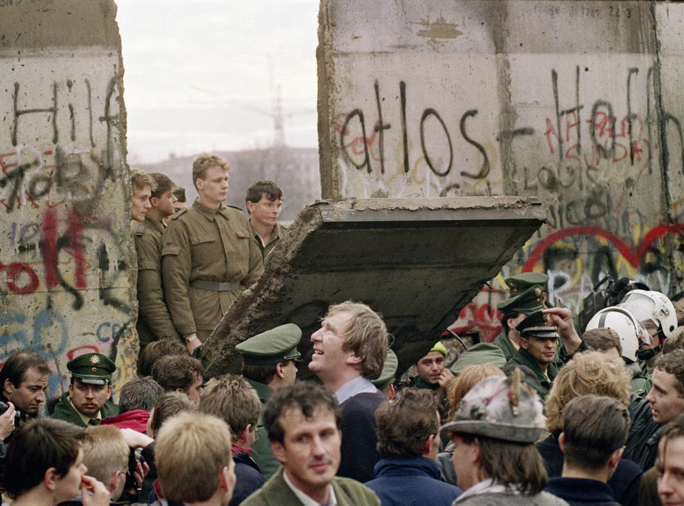 11 November 1989: East German border guards demolish a section of the wall to open a new crossing point between East and West Berlin