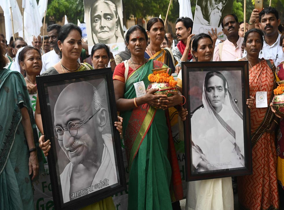 Activists hold portraits of Indian independence icon Mahatma Gandhi and his wife Kasturba Gandhi as they mark his 150th birth anniversary with a peace march from Delhi to Geneva
