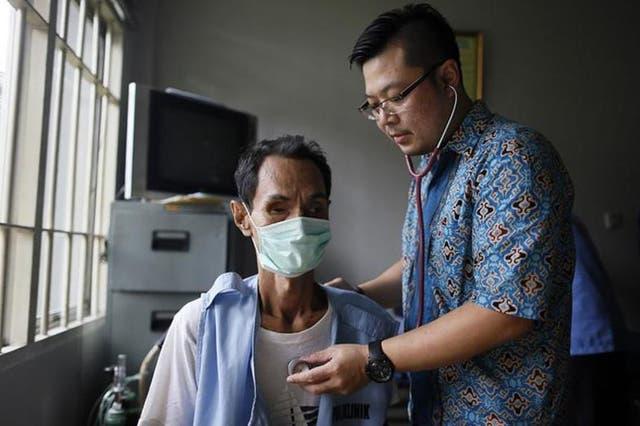 Global disease: a doctor treats a TB prisoner in Jakarta, Indonesia