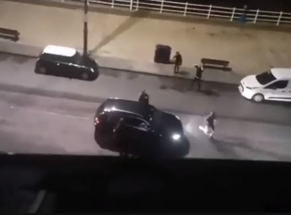 Passers-by were seen trying to stop the car before they were threatened into retreating