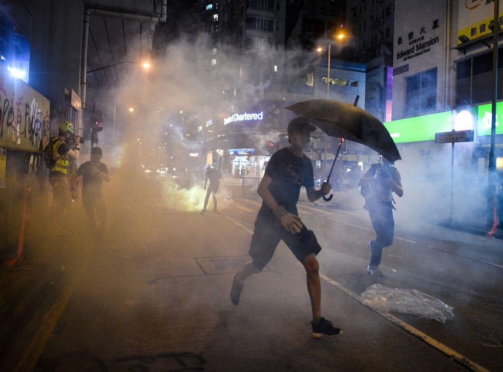 Protesters react after police fired tear gas in the Mong Kok district in Hong Kong on October 7, 2019
