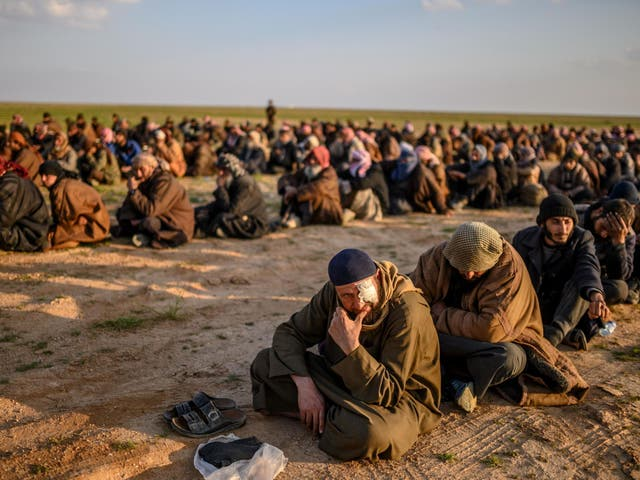Suspected Isis fighters wait to be searched by the Kurdish-led SDF
