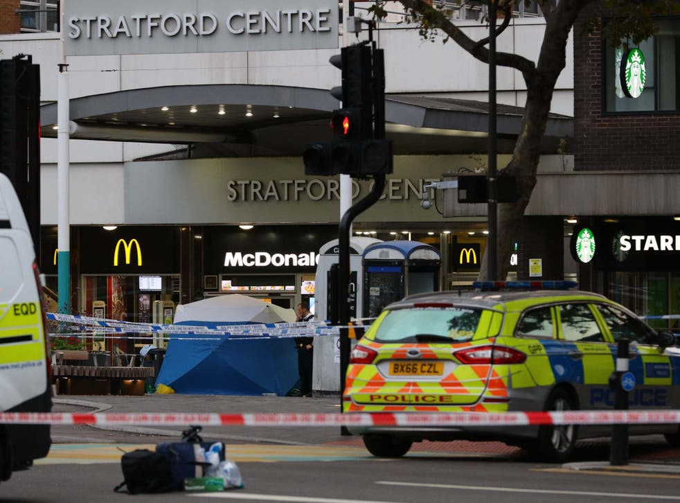 Police set up a forensic tent in front of an entrance to the Stratford Shopping Centre