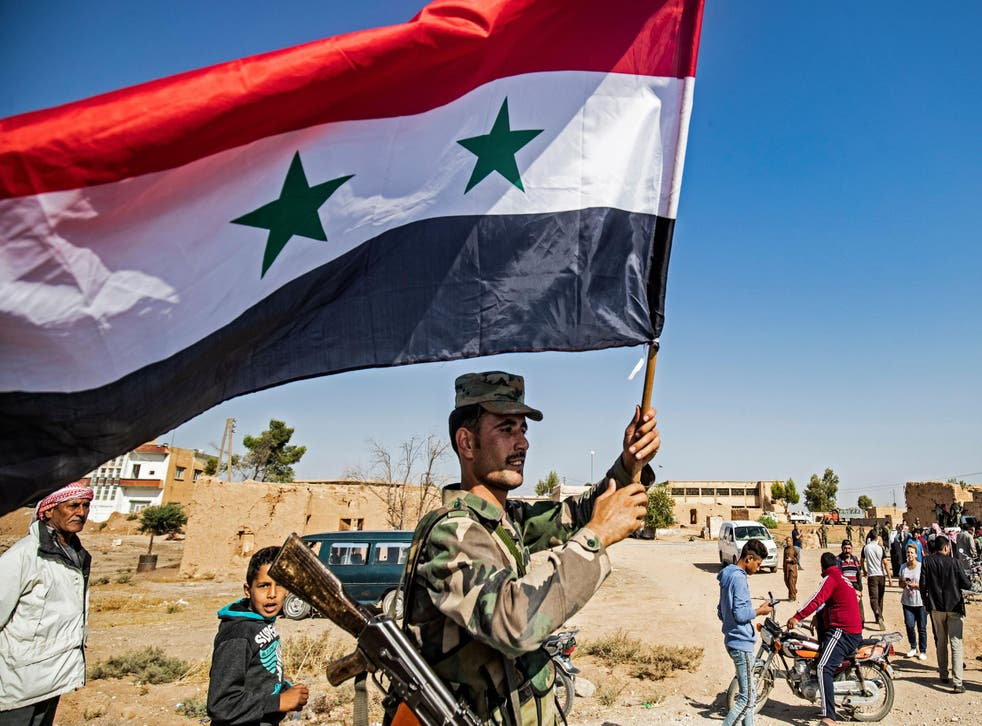 A Syrian regime soldier waves the national flag a street on the western entrance of the town of Tal Tamr in the countryside of Syria's northeastern Hasakeh province