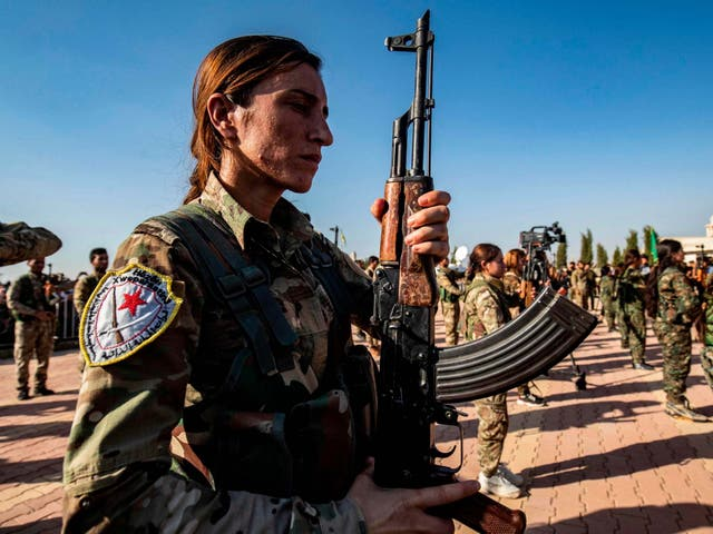 Kurdish fighters attend a funeral for political leader Hevrin Khalaf, who was reportedly executed by pro-Turkish militants in northeastern Syria