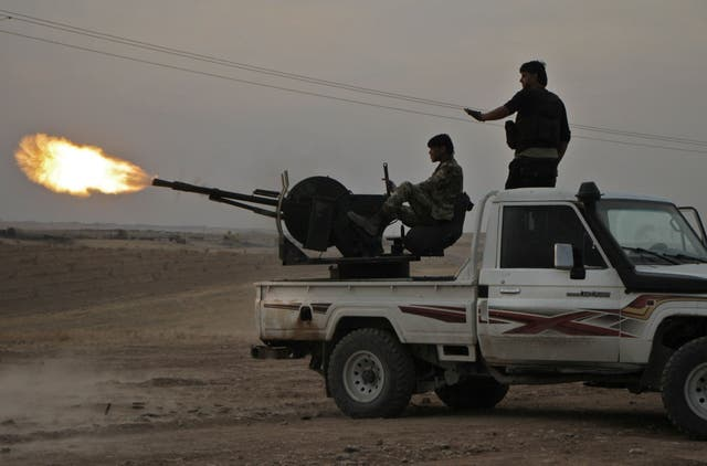 Turkish-backed Syrian fighters fire a truck mounted heavy gun near the town of Tukhar, north of Syria's northern city of Manbij, on Monday
