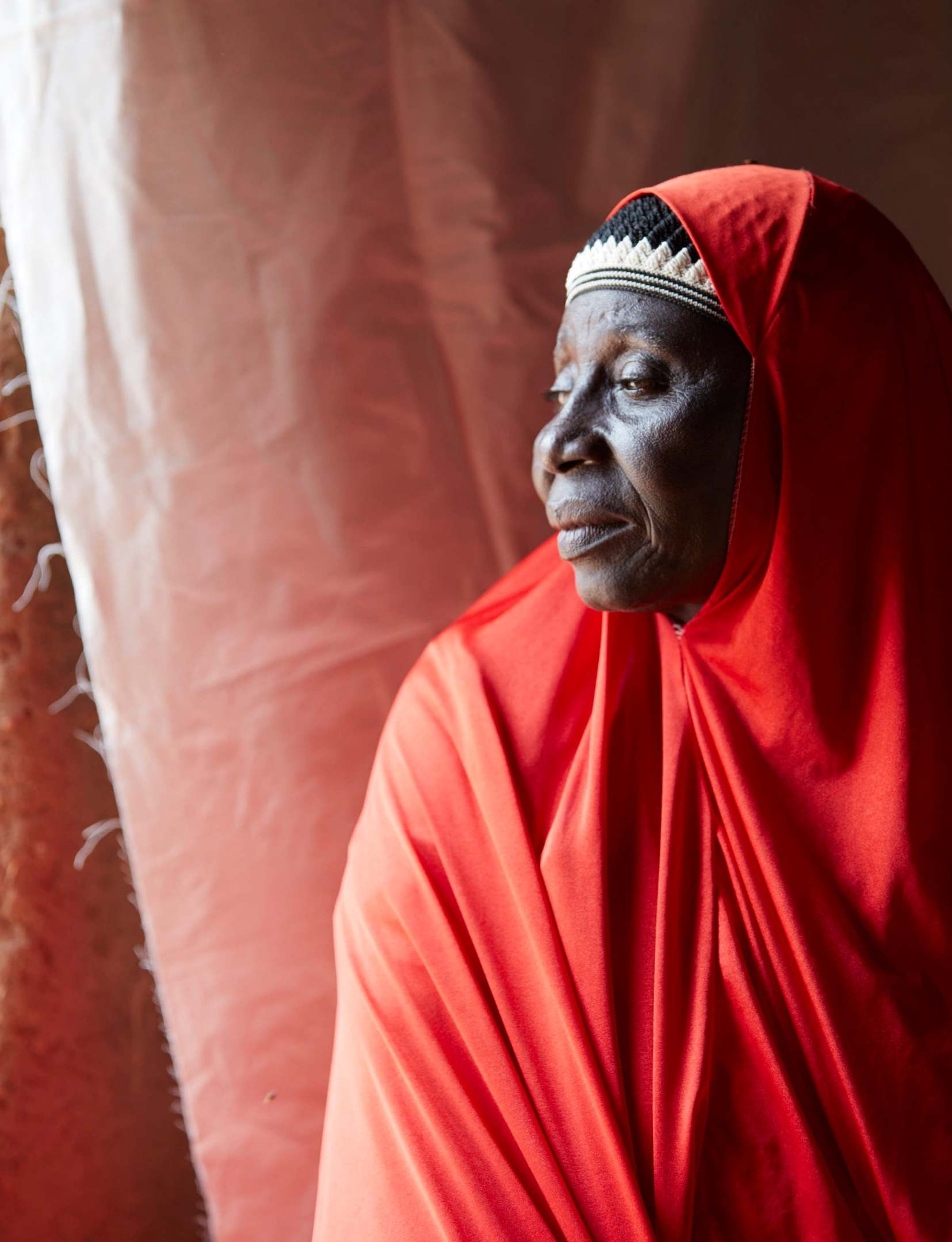 Aissa Garba, 65, gazes out of the window of her home in Tombokiery village, southern Niger