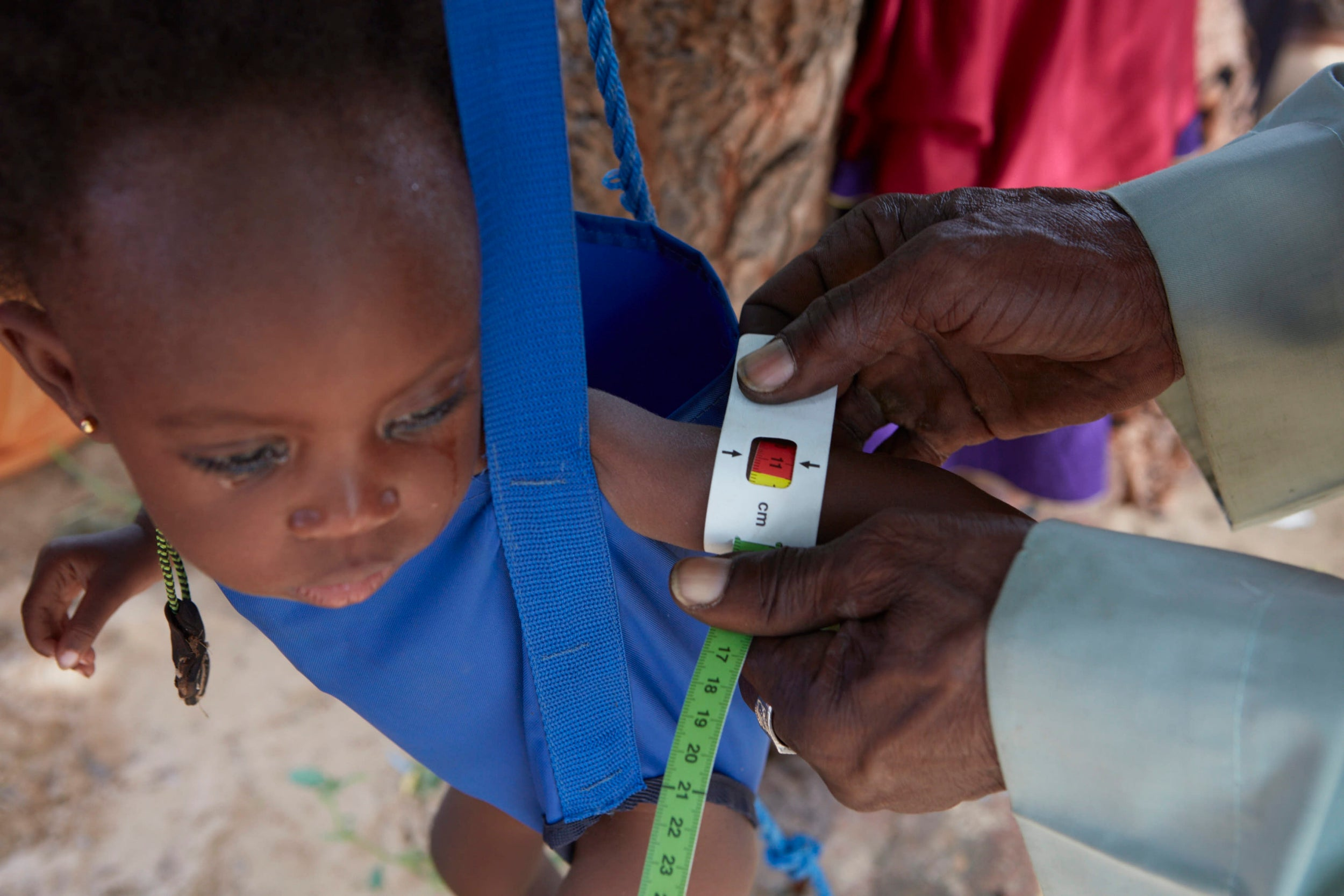 A child is weighed and arm measured at the Red Cross nutrition centre in the village of Kiéché, southern Niger