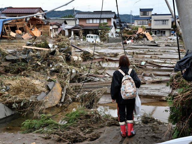 A woman looks at flood-damaged homes in Nagano after Typhoon Hagibis
