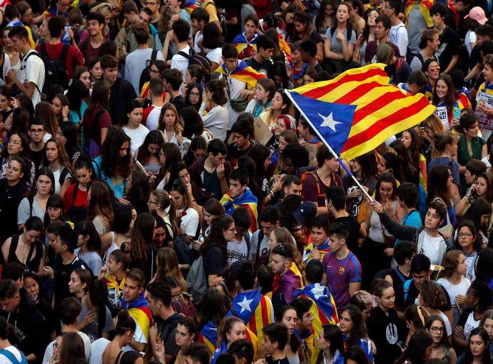 Students wave a Catalan pro-independence flag as they protest during a demonstration in front of the police headquarters in Barcelona