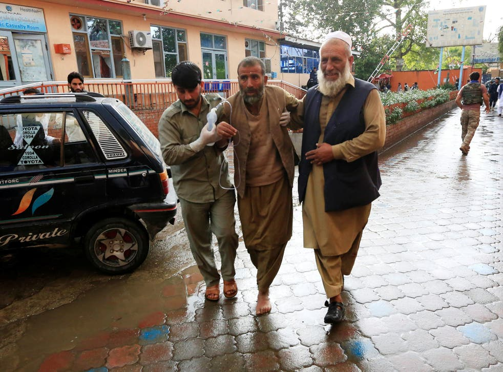 Men carry an injured person to a hospital after the bomb blast rocked the mosque in the Nangarhar Province
