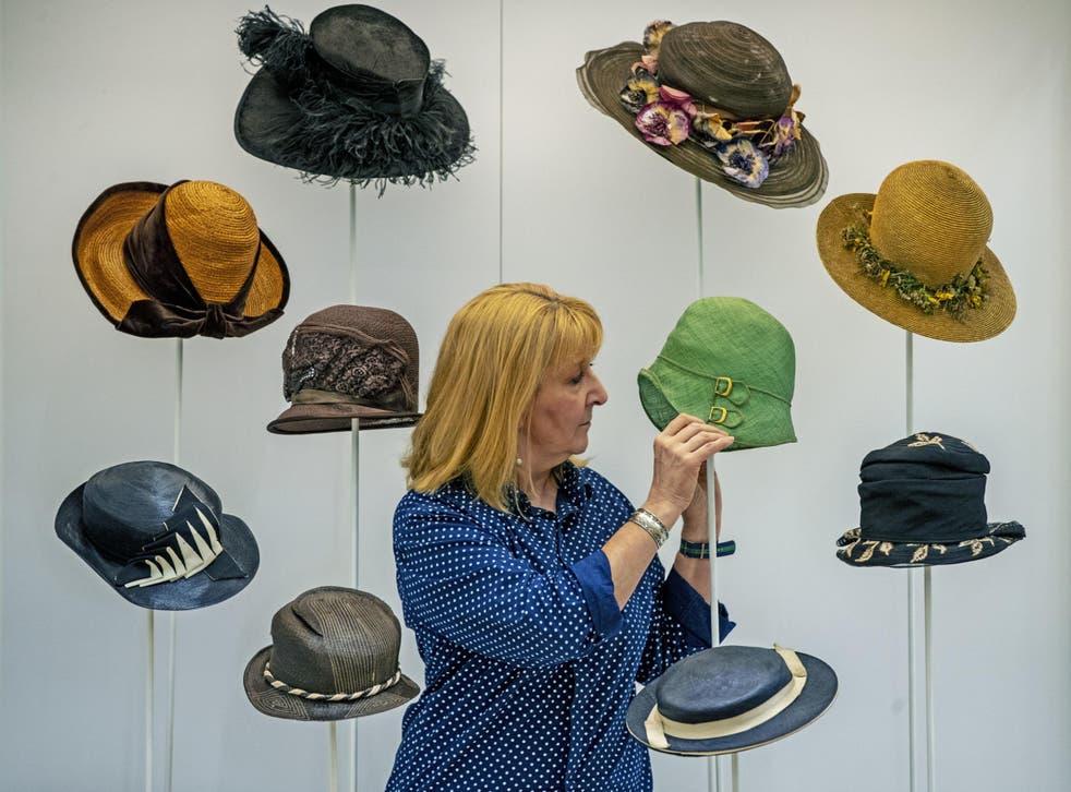 Curator Pauline Rushton examines one of Emily Margaret Tinne's many hats
