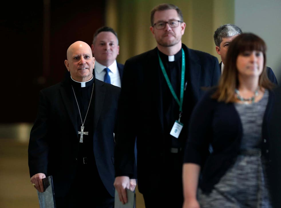Samuel Aquila, archbishop of the Denver diocese of the Roman Catholic Church, left, trails Very Rev. Randy Dollins, vicar general, into a news conference at which a plan was revealed to have a former prosecutor review their diocese's sexual abuse files
