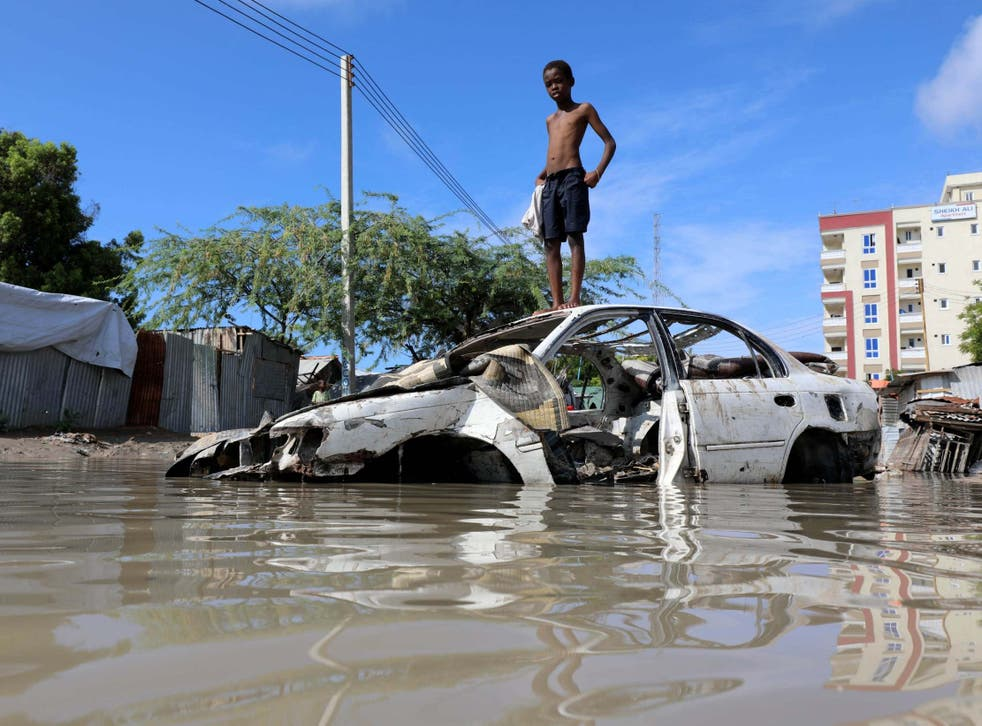 A Somali boy stands on a junk vehicle after heavy rain flooded their neighbourhood in Mogadishu, Somalia, 21 October, 2019.