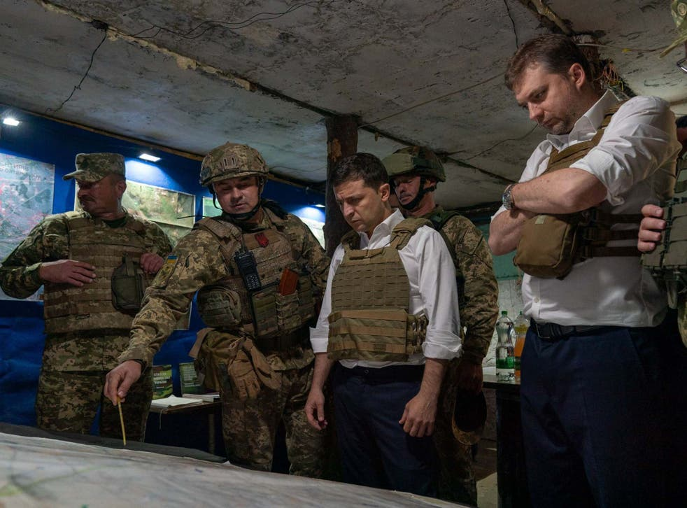 Volodymyr Zelensky (centre) talking with officers at a map during his visit to the Donetsk region