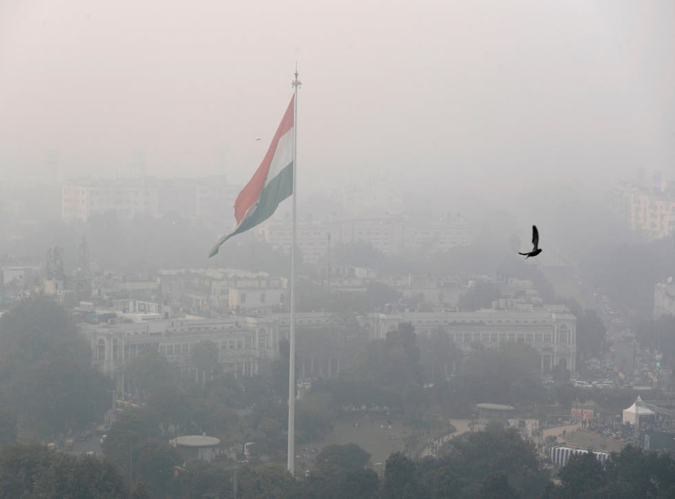 A bird flies past as Delhi's skyline is seen enveloped in smog and dust on Friday
