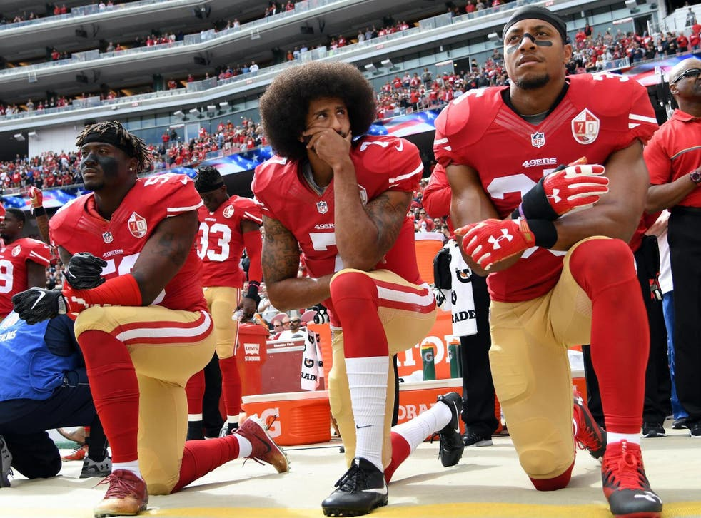 Eli Harold, Colin Kaepernick and Eric Reid of the San Francisco 49ers kneel on the sideline during the anthem