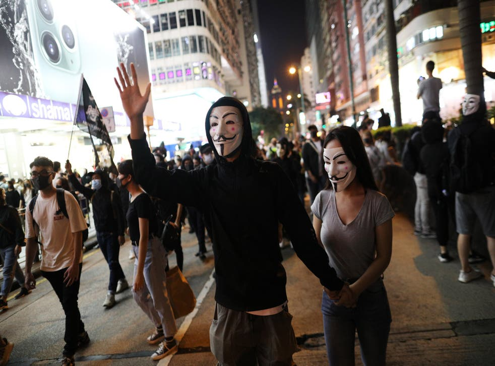Protesters wear 'Guy Fawkes' masks as they take part in a rally in Hong Kong on Tuesday